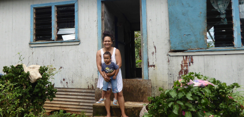 Mother and child by house in Tonga