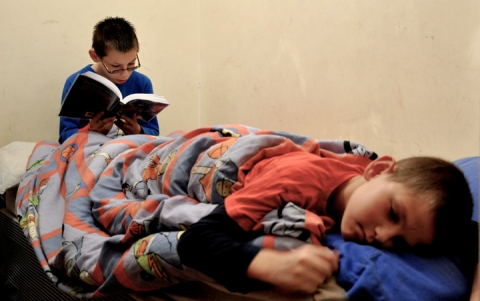 Two young boys, one reading, share beds